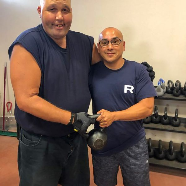 two men standing next to one another holding a kettle bell