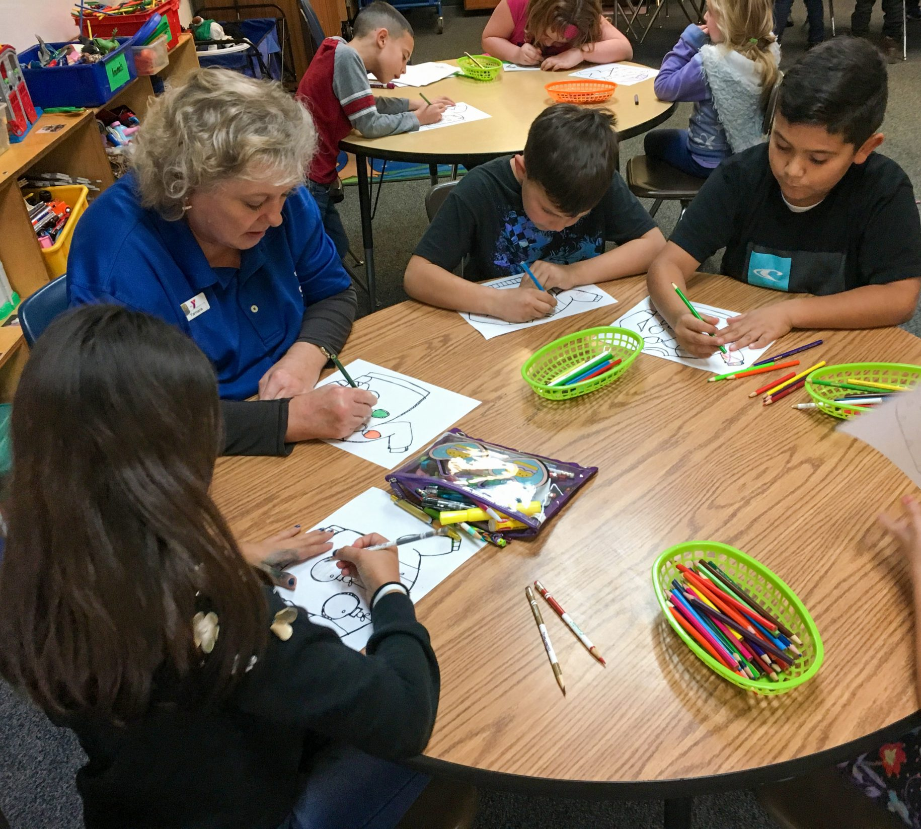 three children coloring pictures with an adult female Y staff member