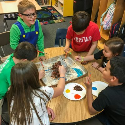 six elementary children painting a volcano