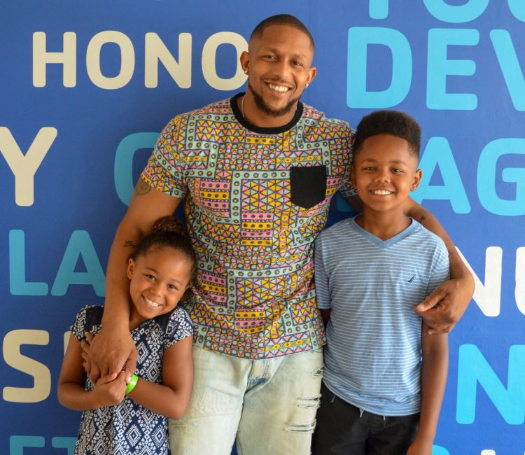 father and children smiling in front of blue wall